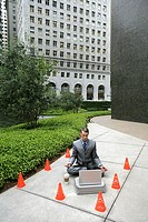 Young businessman meditating in front of laptop with traffic cones