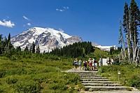 A group of hikers and Mount Rainier under blue sky, Washington, USA