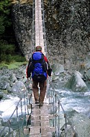 Man on a suspension bridge above the Rees Dart River, Mount Aspiring National Park, South Island, New Zealand, Oceania