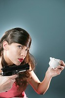 Young woman shooting piggybank from gun, portrait