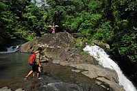 A man wading through a river near a waterfall, North Bali, Indonesia, Asia