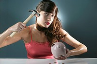 Portrait of a young woman about to break a piggy bank with hammer