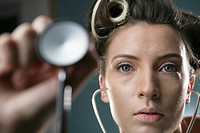 Close_up portrait of a young woman holding a stethoscope