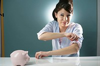 Young woman sitting by piggybank on table adjusting her sleeves