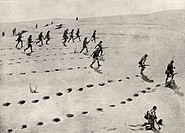 The desert phase of the South-West African campaign  Union troops plodding forward under fire  The man lower right has been hit  Puffs of sand from bu...