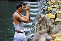 A Balinese man  ritually washing in a pool at Tirtal Empul temple, considered Bali's holiest spring in Tampaksiring, Bali