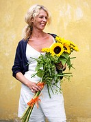 Woman with sunflowers against a yellow wall Sweden.