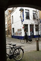 Cyclist passing by a religious image on Steenhouwersvest street corner, Antwerp, Flanders, Belgium
