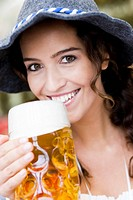 Young Woman With Hat Drinking Beer