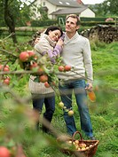 Man and woman picking apples cuddling