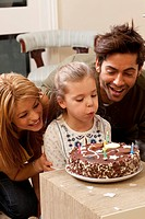 parents and child blowing out candles