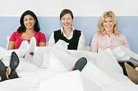 Three female colleagues sitting in bed