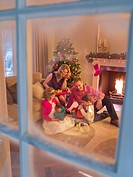 Family opening Christmas gifts in living room (thumbnail)