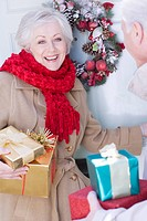 Couple with Christmas gifts standing at door