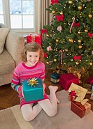 Girl holding gift by Christmas tree