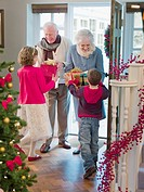 Grandparents giving grandchildren Christmas gifts in doorway (thumbnail)