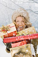 Snow falling on laughing woman holding Christmas gifts