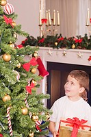 Boy holding gift and looking up at Christmas tree