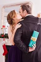 Woman hugging man holding Christmas gift behind back