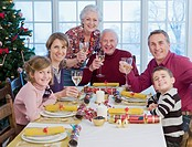 Multi_generation family holding wine glasses at Christmas dinner