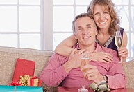 Couple drinking champagne near Christmas gifts