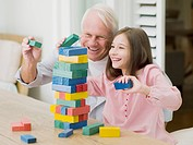 Grandfather and granddaughter stacking blocks