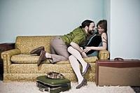 Man embracing woman on living room sofa with luggage