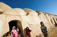Family in fronf of old traditional hive houses, Fah village near Aleppo, Syria