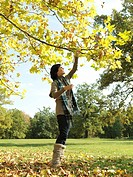 Woman picking leaves off Autumn branches