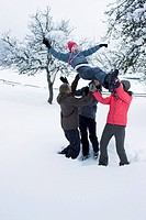 Group of young people throwing a girl in the sky in snowy landscape smiling and laughing.
