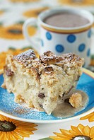 A piece of bread pudding with a cup of cocoa