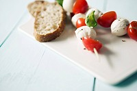 Cutting board with tomato and mozzarella skewers