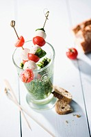 Mozzarella and tomato skewers with glass of pesto