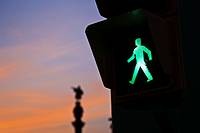 Spain, Cataluna, Barcelona, La Barceloneta, Green man crossing traffic signal and Monument a Colom in the background at sunset