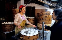 China, Shanghai, Dajing Lu District and market, saleswoman of steam baozi