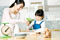 Girl and mother baking in kitchen
