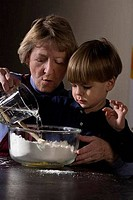 Senior woman making cookies with her grandson