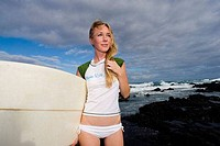 Young woman carrying a surfboard, Hawaii, USA