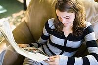 Teenage girl reading a newspaper