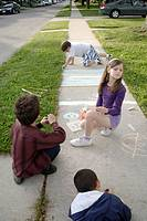 Canada, Ontario, Windsor. Three boys and one girl drawing with chalk on a sidewalk during the summer.