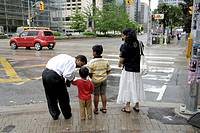 Canada, Ontario, Canada. A father talks to his child as the rest of the family waits to cross at an intersection