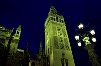Spain, Andalusia, Sevilla, night view of la Giralda Tower, former Almohad minaret of the Great Mosque converted into cathedral steeple topped by the s...