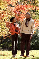 African couple walking in park in autumn