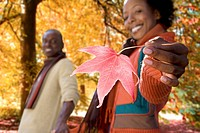 African woman holding red autumn leaf