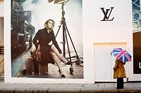 United Kingdom, London, Mayfair, pedestrian with a Union Jack umbrella looking at an advertisement for Louis Vuitton with Catherine Deneuve