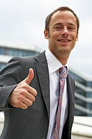 Half body photograph of smiling young, caucasian business man in suit and tie, with thumbs-up sign, Hamburg, Germany, Europe