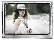 A young woman wearing a straw hat holding daisies