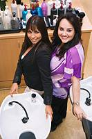 Two hispanic businesswomen at beauty parlor, smiling, portrait