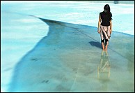 A teenage girl standing in an empty swimming pool