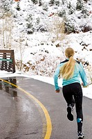 Woman running on winter trail in snowy scenery Utah USA